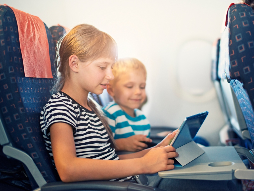 Brother and sister playing with tablet in plane